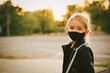 Little cute girl wearing black mask outdoors. Covid 19. School. Girl in the park in mask.