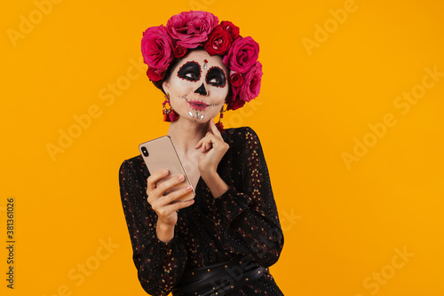 Obraz na plátně Photo of girl in halloween makeup and flower wreath using mobile phone