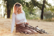 Portrait Of A Beautiful Young Woman Sitting On The Dry Grass Leanher Head On Saxophone, Romantic Blonde Girl Close Eyes And Relaxing