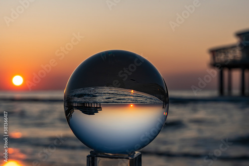 The setting sun at the Pier in Scheveningen is inverted in the Lens Ball