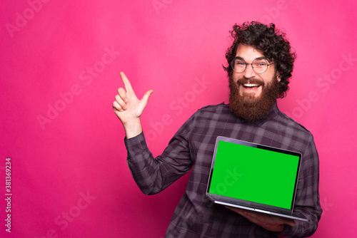 Fotografie, Obraz Blank green screen on laptop, happy man with beard smiling and pointing away and