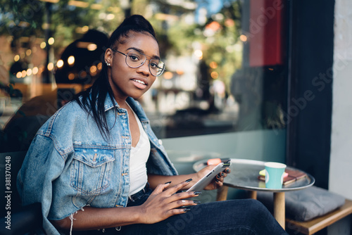 Fototapeta Positive trendy dressed woman in spectacles looking at camera using modern digital tablet connected to 4G internet, smiling female 20s african american looking at camera checking notifications obraz