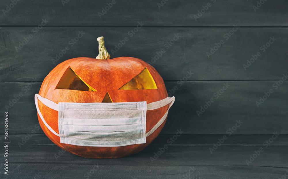 Fototapeta Halloween pumpkin wearing a protective medical mask. New normal concept