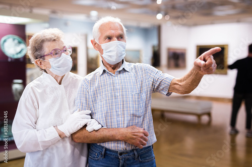 Foto mature couple in mask protecting against covid examines paintings on display in
