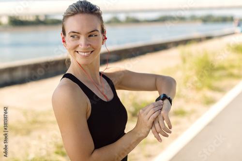 Fototapeta Happy athletic woman using fitness tracker outdoors. obraz