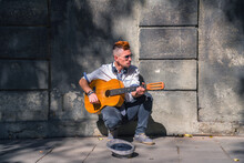 Male Street Musician Playing G...