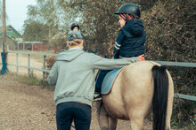 A Child With Special Needs Is Riding With A Close Supervision Teacher] This Is A Treatment Called Hippotherapy, Life In The Education Age Of Disabled Children, Happy Disability Kid Concept.