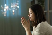 Profile Of A Woman Praying At Night At Home