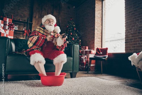 Fototapeta Full length photo funny grey white beard hair santa claus sit couch rest x-mas d