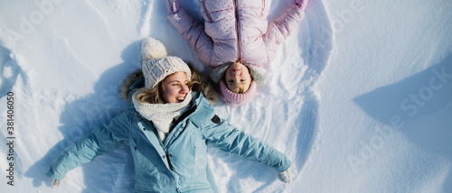 Obraz Top view portrait of cheerful mother with small daughter lying in snow in winter nature. - fototapety do salonu