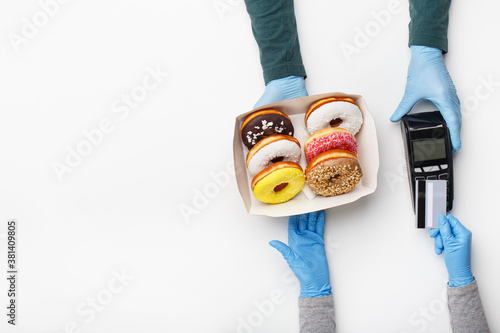 Fototapeta Fast food to go and order payment during covid pandemic. Waiter in rubber gloves gives box of colorful donuts, client pays with credit card at terminal obraz