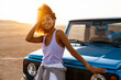 Image of cheerful african american woman smiling while travelling with car on desert