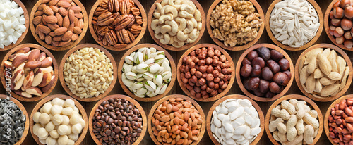 Fototapeta assorted nuts and seeds in wooden bowls, food background. obraz