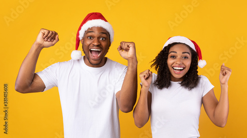 Photo Black Couple In Santa Hats Shaking Fists Over Yellow Background