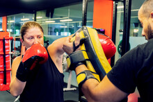 Young Girl Training Kickboxing With A Trainer To Practice Self Defense. She Is Wearing Black And Red Boxing Gloves