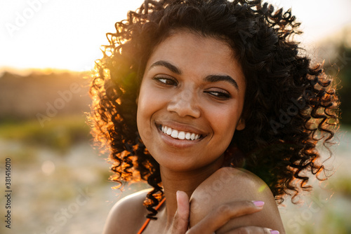 Smiling young african woman walking at the beach Canvas Print