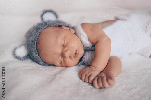 Fototapeta Cute emotional newborn little baby boy sleeping in crib in a knitted suit with ears