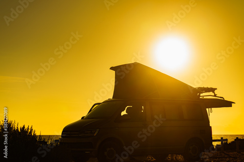 Camper van with tent on roof at sunset Fotobehang