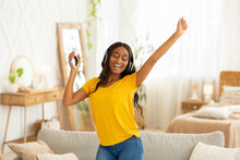 Happy African American Lady With Headphones And Smartphone Dancing To Beautiful Music At Home