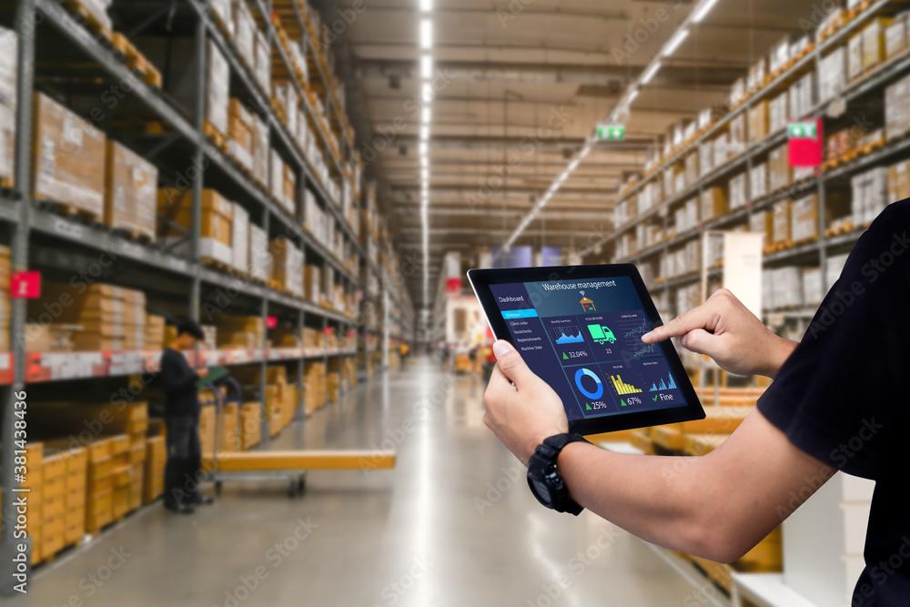 Fototapeta Smart warehouse management system.Worker hands holding tablet on blurred warehouse as background