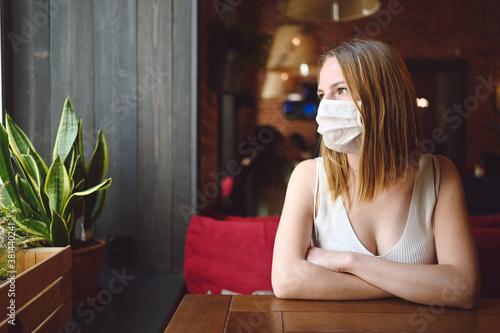 Young beautiful girl is sitting in a cafe or restaurant and waiting for her order wearing face protective mask for flu virus prevention Fototapet