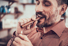 Man Sits With A Cigar In His M...