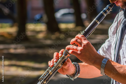 Photo Close up young man playing clarinet on walking street