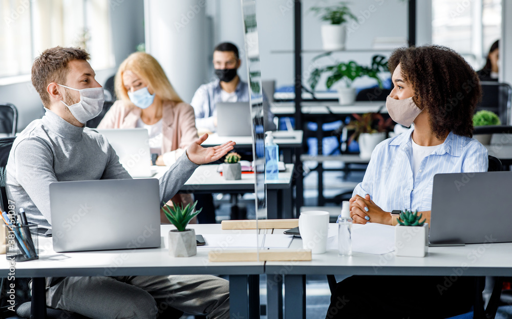 Fototapeta Communication and meeting in office after returning from quarantine. Young guy and african american woman in protective mask talking through glass board at workplace