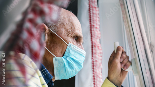 Fototapeta bald pensioner in mask holds window handle to air room
