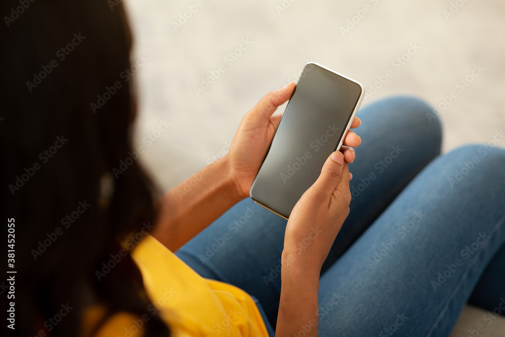 Fototapeta African American lady holding smartphone with empty screen whileresting on sofa at home, mockup for mobile app design