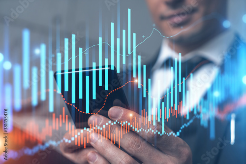 Trader in office working with Smartphone, FOREX graph hologram to analyze market behavior, typing phone Fotobehang