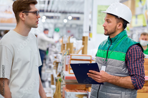 Canvas Print side view on supervisor and customer discussing in store, worker in uniform cons
