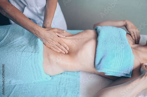 Fototapeta Young unrecognizable woman lying on massage table and enjoying therapeutic massage
