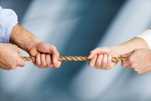 Business People Pulling Rope In Opposite Directions