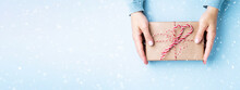 Female's Hands Holding Gift Box Decorated With Candy Cane On Blue Background. Christmas And New Year Banner With Snow.