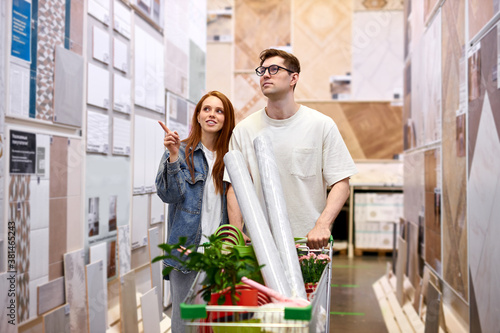 Fototapeta couple choosing linoleum for home, caucasian man and woman shopping together, redhead female points finger at the best one obraz