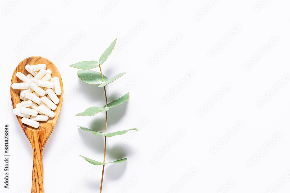 Fototapeta Collagen capsules in the wooden spoon and aromatic eucalyptus twig on white background. Minimalism style composition. Natural herbal pills on white background.