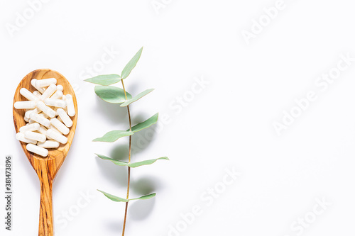 Fotomural Collagen capsules in the wooden spoon and aromatic eucalyptus twig on white background