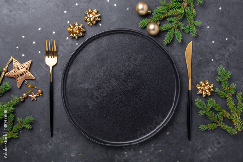 Christmas table setting with empty black ceramic plate, fir tree branch and gold accessories on black stone background. Top view. Copy space