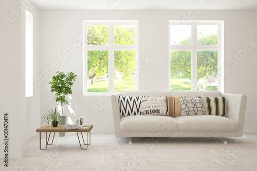 Fototapeta White living room with sofa and summer landscape in window