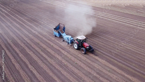 Photographie Almond combine harvester processing a field and Picking dry Almonds from the ground and blowing the dust