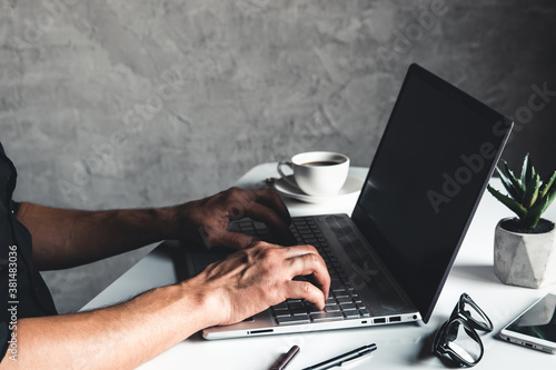 A man types on a laptop, business concept, glasses, a cup of coffee and a pen on a gray background Canvas