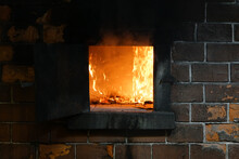 Roaring Fire Burning Brightly In Fireplace, With Ashes And Red Embers.