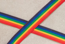 Two Jute Stripes Of Colorful Rainbow Color, Lying Crosswise On A Gray Background