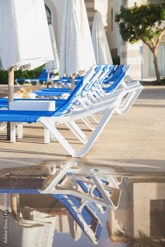 white sun loungers stand in a row reflecting in a puddle Canvas Print