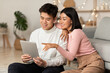 canvas print picture Japanese Boyfriend And Girlfriend Using Digital Tablet Sitting At Home