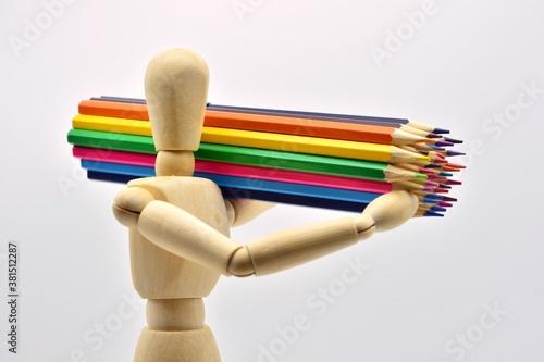 Fototapeta Maniquí de madera cargado con lápices de colores