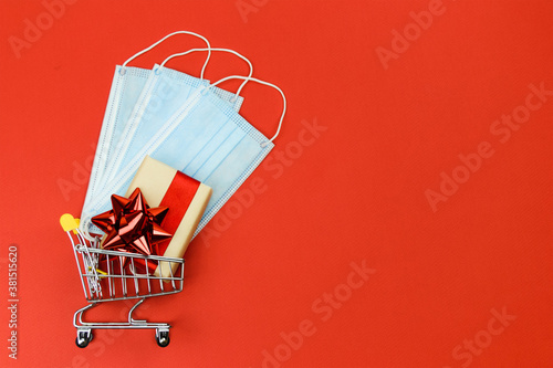 Fototapeta Gift box with a red bow and medical face masks lie in a shopping trolley