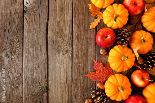 Fototapeta Fall side border with pumpkins, leaves and apples. Above view on a rustic dark wood background with copy space. obraz