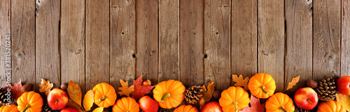 Fototapeta Fall border with pumpkins, leaves and apples. Top view on a rustic dark wood background with copy space. obraz na płótnie
